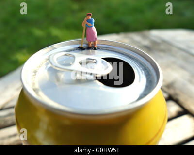 Miniature cleaning lady leaning on broomstick on top of soda can with blurred background. Business concept - Stock Photo