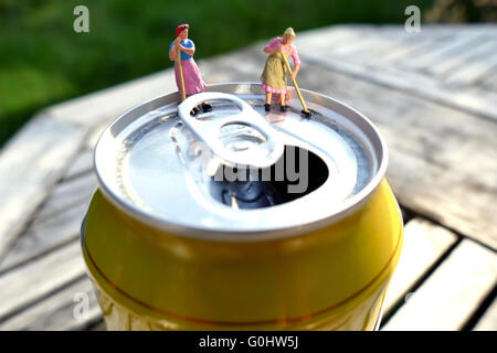 Miniature cleaning women sweeping on top of soda can with blurred background. Business concept - Stock Photo