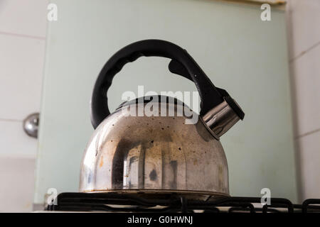 Dirty kettle on a kitchen - Stock Photo