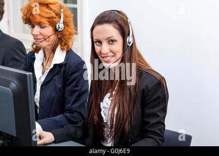 friendly callcenter agent operator with headset telephone - Stock Photo