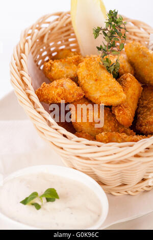 Crumbed chicken nuggets in a basket - Stock Photo