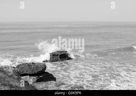 A wave crashing on a rock formation in the ocean - Stock Photo
