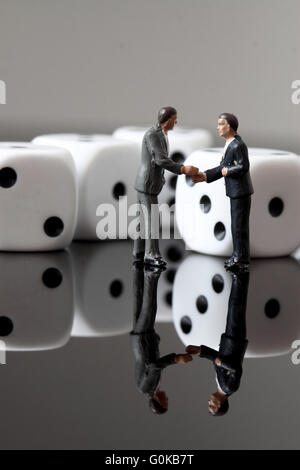 Miniature businessmen standing in front of dice reflected - Stock Photo