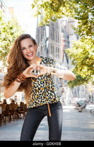 Get ready to exciting weekend at Barcelona. Portrait of smiling woman tourist near Sagrada Familia showing heart - Stock Photo