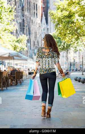 Getting unique trends of Barcelona. Seen from behind fashion-monger woman with shopping bags walking down the street - Stock Photo