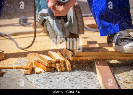 Carpenter using an electric saw cutting small wooden figures - Stock Photo