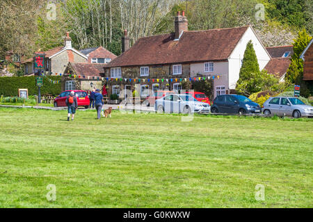 Red Lion public house as viewed from across the village green at Fernhurst West Sussex, showing dog walkers on green. - Stock Photo