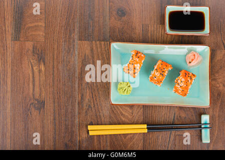 Sushi rolls with masago, served on turquoise plate with pickled ginger, soy sauce and chopsticks on wooden table. - Stock Photo