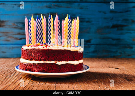 a red velvet cake topped with some unlit candles on a rustic wooden table - Stock Photo