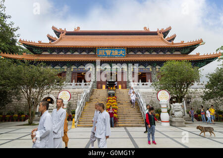 Monks and tourists in front of the Main Shrine Hall of Buddha at the Po Lin Monastery on Lantau Island in Hong Kong, - Stock Photo