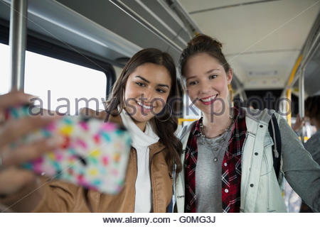 Teenage girls taking selfie cell phone on bus - Stock Photo