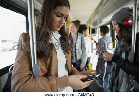 Teenage girl texting cell phone standing on bus - Stock Photo