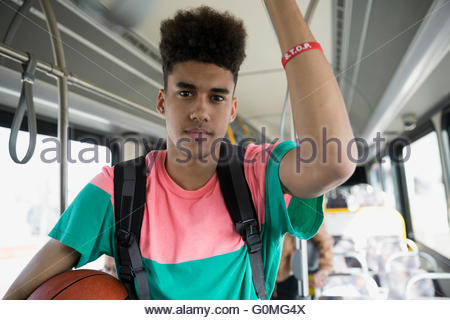 Portrait serious young man with basketball riding bus - Stock Photo