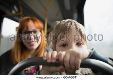 Portrait curious boy riding bus with mother - Stock Photo