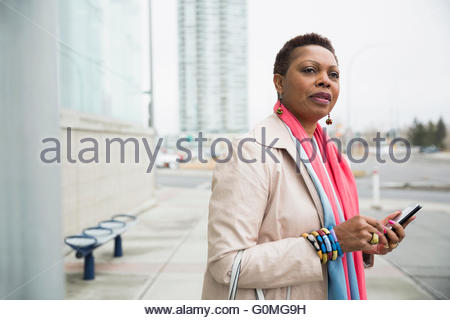 Woman with cell phone waiting at bus stop - Stock Photo
