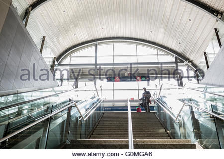 Businessman with suitcase top of stairs train station - Stock Photo