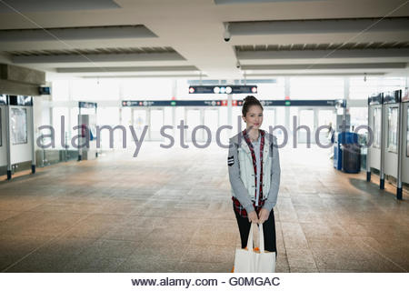 Portrait teenage girl reusable shopping bag train station - Stock Photo