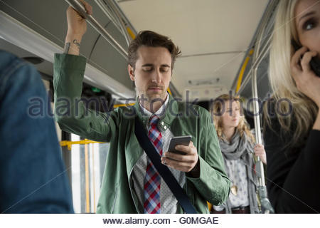 Businessman texting with cell phone standing on bus - Stock Photo
