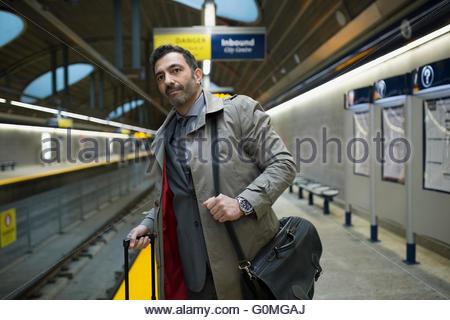 Businessman with suitcase briefcase waiting subway station platform - Stock Photo