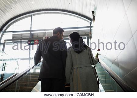 Couple ascending escalator at train station - Stock Photo