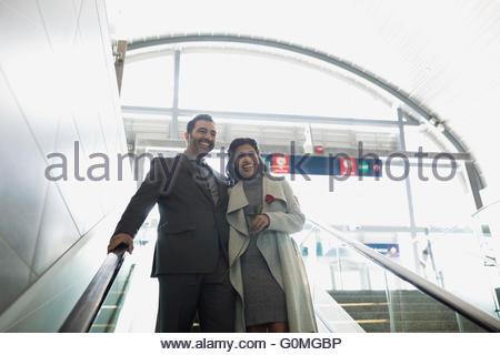 Smiling couple descending escalator at train station - Stock Photo