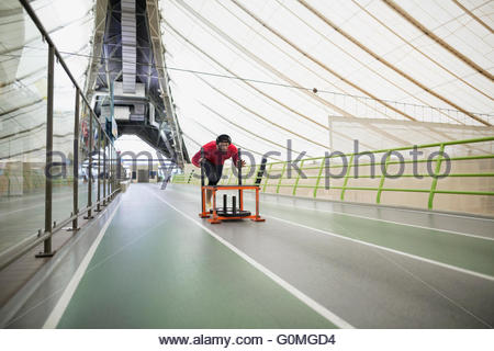 Runner pushing sprinting sled on indoor track - Stock Photo