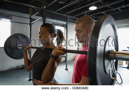 Personal trainer guiding woman weightlifting barbell - Stock Photo