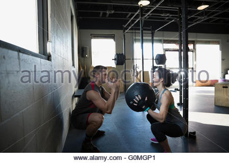 Personal trainer guiding woman squatting with medicine ball - Stock Photo
