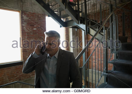 Businessman talking on cell phone in stairwell - Stock Photo