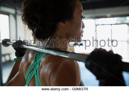 Close up woman weightlifting with barbell at gym - Stock Photo
