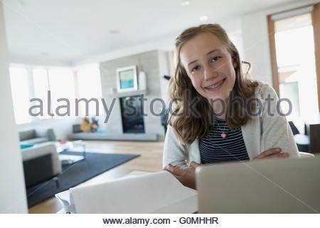 Portrait smiling girl doing homework at home - Stock Photo