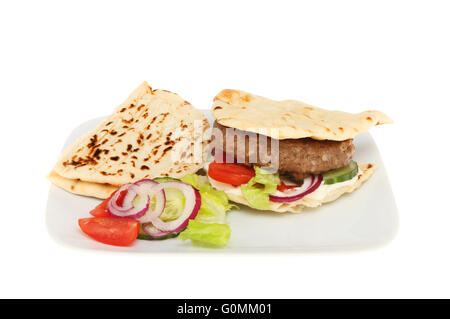Beef burger with salad in a flatbread on a plate isolated against white - Stock Photo
