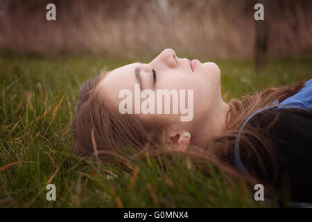 Pretty teenage girl lying down on grass with her eyes closed - Stock Photo