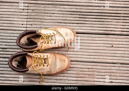 Close-up of Vintage old pair boots on wood floor - Stock Photo