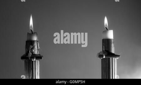 2 Burning candles in Empire Style candle holders in black and white soft focus - Stock Photo