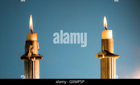 2 Burning candles in Empire Style candle holders in color hard focus - Stock Photo