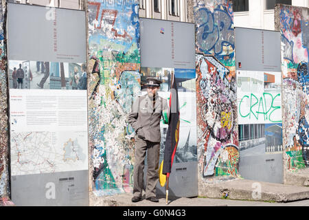 Part of the Berlin Wall at Potsdamer Platz 2016, with tourists and a man dressed up as a former East German soldier - Stock Photo