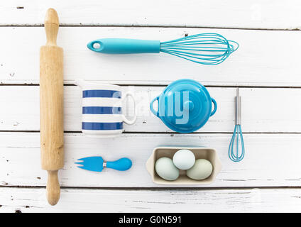 Blue Kitchen Tools on a rustic white wooden table top - Stock Photo