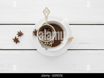 Cup of Tea with a vintage strainer and Star Anise on a rustic white wooden background - Stock Photo