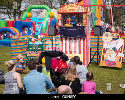 People watching a traditional Punch and Judy puppet show at a summer fair - Stock Photo