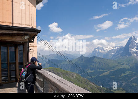tourist photographing the Jungfrau massif from Birg station on the way to Schilthorn mountain top - Bernese Canton - Stock Photo