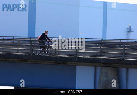 Young male cyclist on a bridge in front of Palm Paper factory in King's Lynn, Norfolk, UK. - Stock Photo