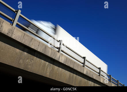 Heavy goods vehicle passing above on a flyover against a blue sky. - Stock Photo