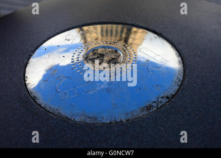 Ashtray outside with the reflection of a church and sky on silvery surface.