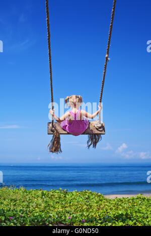 Little baby girl fly high with fun on rope swing on blue sky background on sea beach with waves and surf in tropical - Stock Photo