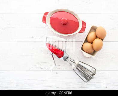 Vintage red metal hand whisk shot on retro white wooden background and bowl of eggs - Stock Photo