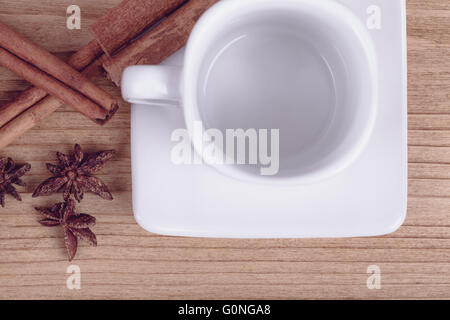 cinnamon and empty white cup, wooden background, pastel retro color - Stock Photo