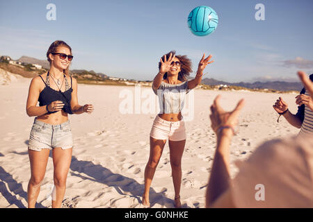 Portrait of young woman playing volleyball with friends on the beach. Group of friends playing volleyball. - Stock Photo