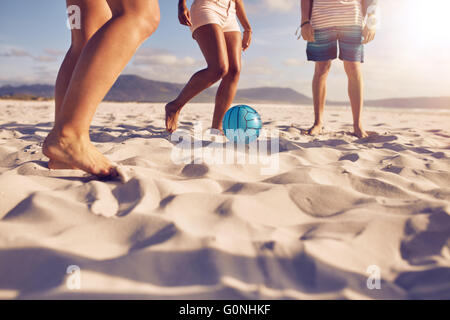Low section portrait of group of friends playing soccer on the beach. a girl is passing the ball to friends. - Stock Photo