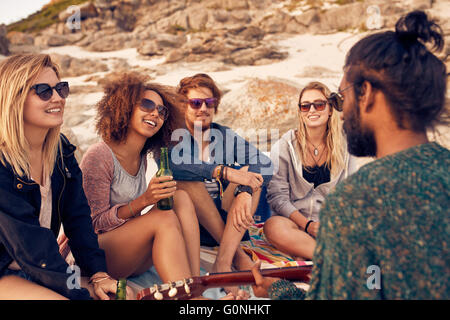 Group of young people listening to a friend playing guitar at the beach. Diverse group of friends hanging out at - Stock Photo